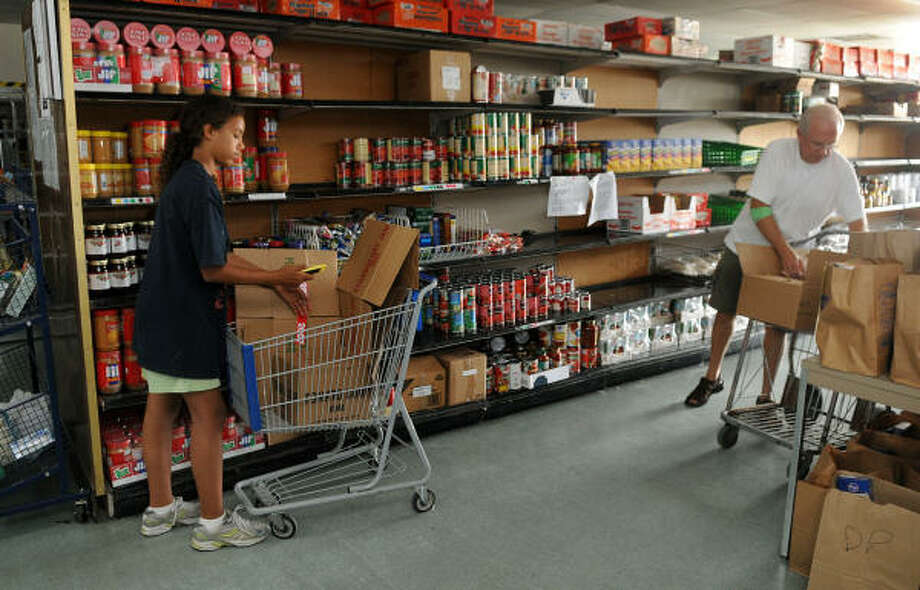 Brandi Ransom, 12, left, a seventh grader at Bammel Middle School, and Mark Stoebner, of Spring, volunteer their time at the Northwest Assistance Ministries in Houston where they were re-stocking shelves in the NAM Food Pantry on Sept. 19. Photo: Jerry Baker, For The Chronicle