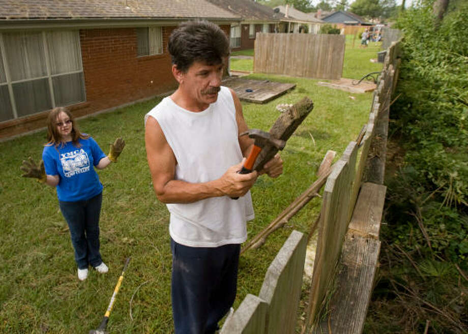 Carl Davis of Spring, (right) and his daughter Cora Davis, 13, work to rebuild their fence which was knocked down during Hurricane Ike. Photo: Steve Campbell, Chronicle