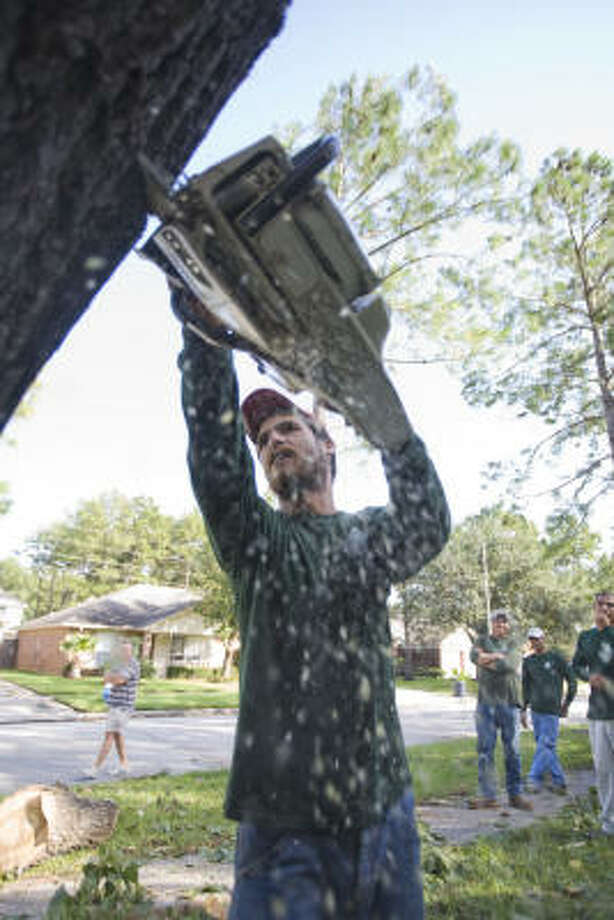 Hugo Figuerroa works with a crew to cut up what is left of a broken tree at the home of John Kearns in the Bridgestone West subdivision in Spring. Photo: Steve Campbell, Chronicle