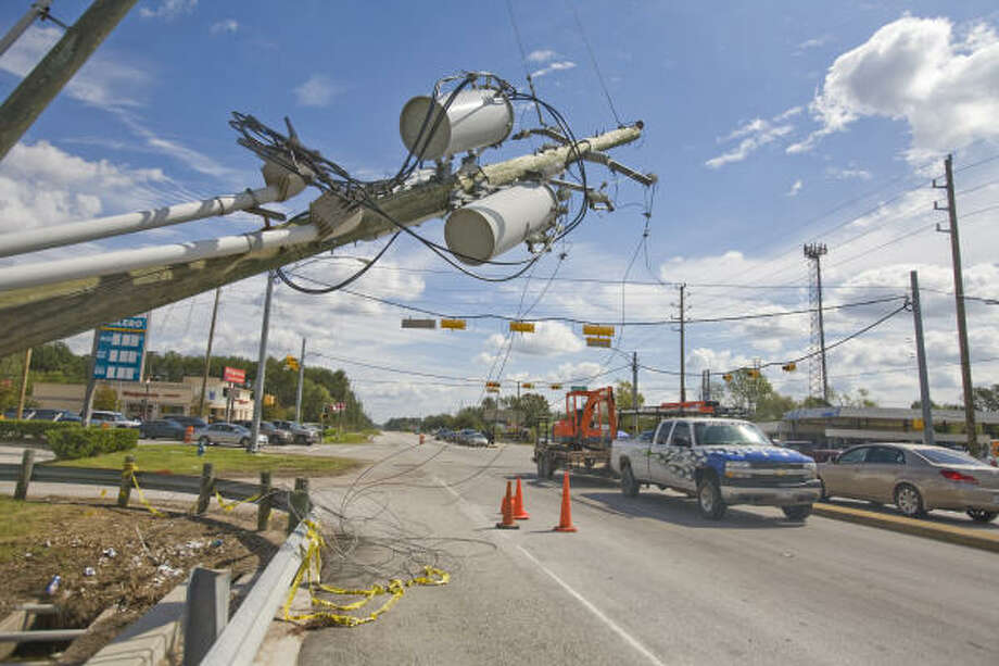 A utility pole with transformers leans partially over Spring Cypress Road near Kuykendahl in Spring. Although the Spring area north of Houston was not hit as hard as some areas of town, power outages and property damage were still problems in the area. Photo: Steve Campbell, Chronicle