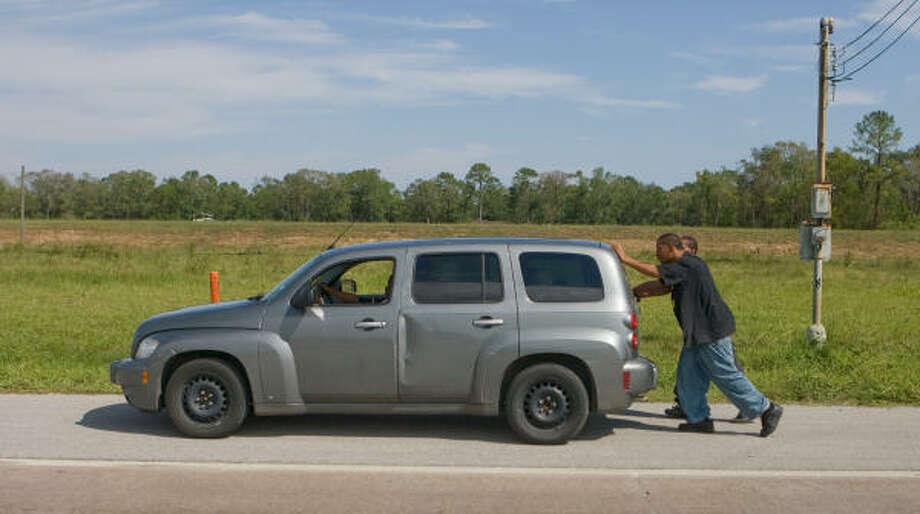 Jevin Gardner conduce su automóvil mientras sus amigos Bobby Lewis y Terry Ross empujan el auto a la gasolinera más cercana en la Beltway 8. Photo: Steve Campbell, Houston Chronicle