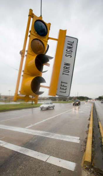 A traffic light at Jones Rd. at Gold Point Dr. hangs by a cord following the winds of Hurricane Ike