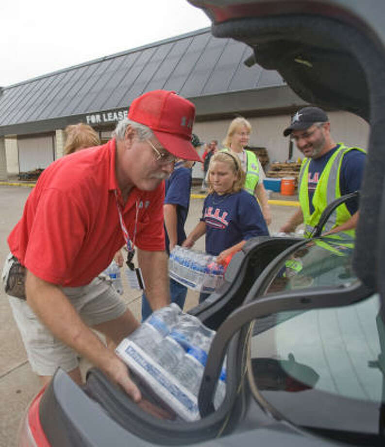Volunteer Rich Obrosky places a case of water in the trunk of a car as Kelly Gist, 11, brings another case. Photo: Steve Campbell, Chronicle