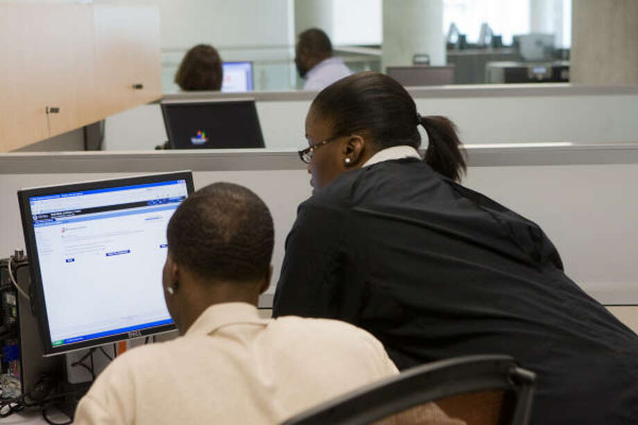 Houston Community College public relations secretary DeJuana Bowie, in black, helps a local resident as HCC's central campus opened a computer lab to anyone who might need to access the internet to apply for FEMA assistance or check on their claims. Photo: R. Clayton McKee, For The Chronicle
