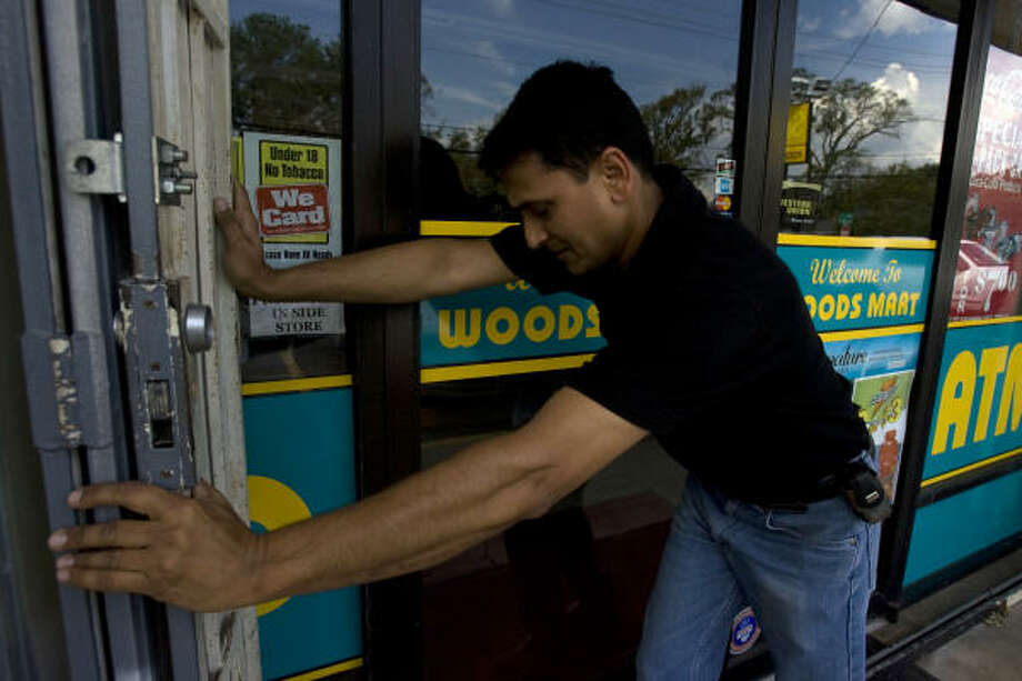 "Nizar Prasla closes up his Woods Foods mini-mart grocery in the Heights, saying that without power, people don't know he is open and he can't keep anything cold. ""We will stay closed until we get electricity back,"" Prasla said on Sept. 24. Photo: Johnny Hanson, Chronicle"