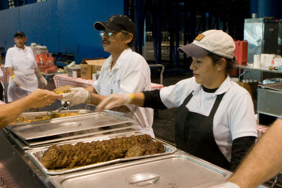 Enrique Hernandez and Susana Zamora serve dinner to hungry relief workers in the George R. Brown Convention Center. Photo: R. Clayton McKee, For The Chronicle