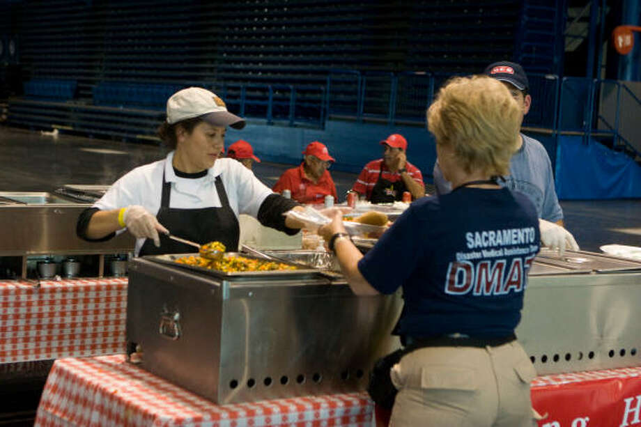 HEB's Susana Zamora serves Judy Mahan of the Sacramento, Cailfornia Disaster Medical Assistance Team at the George R. Brown Convention Center on Sept. 17. Photo: R. Clayton McKee, For The Chronicle