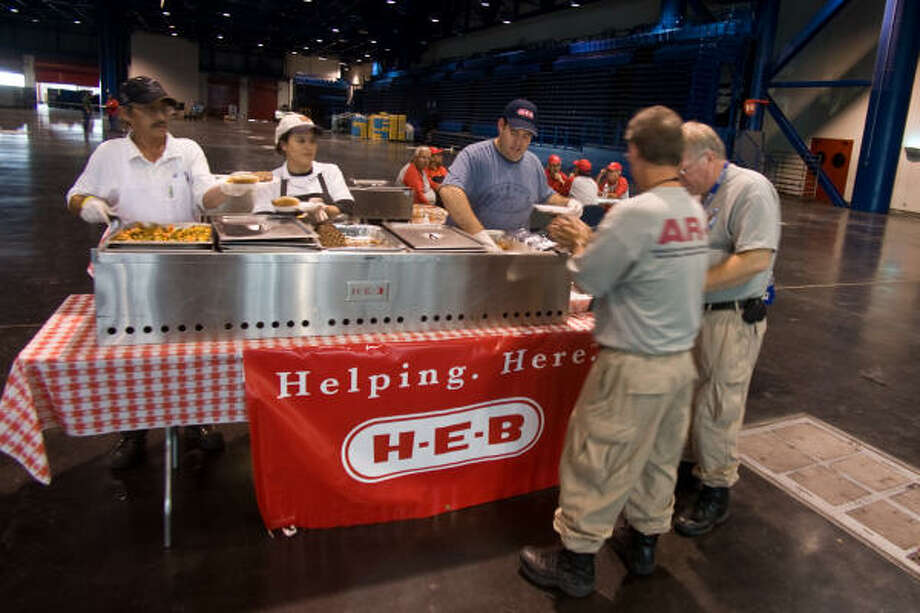 Enrique Hernandez, Susana Zamora and Alex Herrera of HEB serve dinner to Steven Savoy and Joseph Sexson of the Arkansas Disaster Recovery Team from Little Rock. Photo: R. Clayton McKee, For The Chronicle