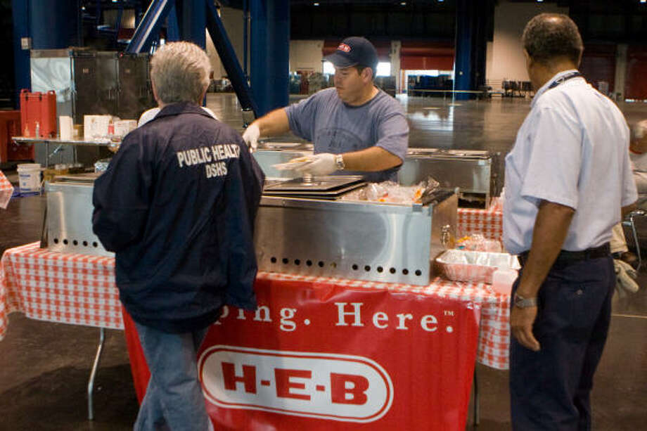 Alex Herrera, HEB truck driver and disaster relief Volunteer, center, mans the serving table at the George R. Brown Convention Center. Photo: R. Clayton McKee, For The Chronicle