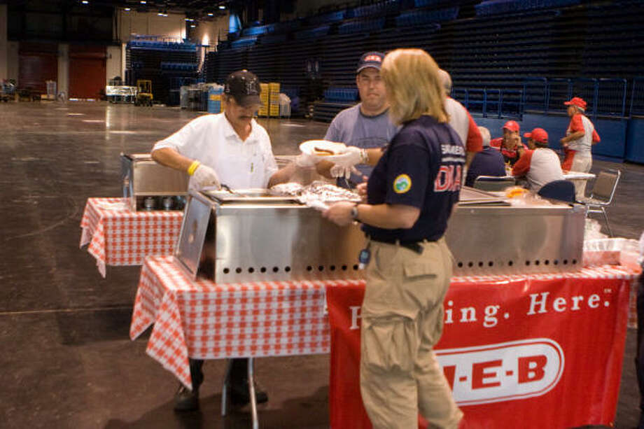 Susana Zamora of HEB serves dinner to a members of the Sacramento, California Disaster Medical Assistance Team. Photo: R. Clayton McKee, For The Chronicle