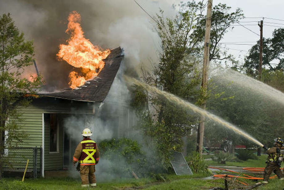 Houston firefighters battle a house fire on 10th Street in the Heights on Sept. 18. Photo: Smiley N. Pool, Chronicle