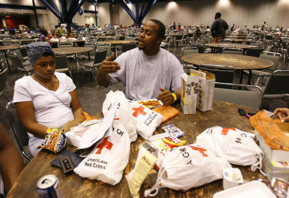 Ben Weems and his girlfriend Tasha Carter sit in the George R. Brown Convention Center Monday after a tree fell on their home during Hurricane Ike. Photo: Karen Warren, Chronicle