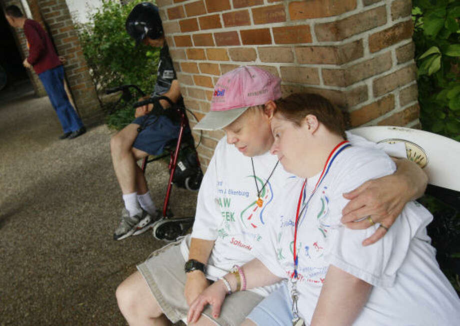 Thomas Claussen embraces girlfriend Christine Futch outside The Center Serving Persons with Mental Retardation in Houston, where the power was still out on Tuesday. Photo: Mayra Beltran, Chronicle