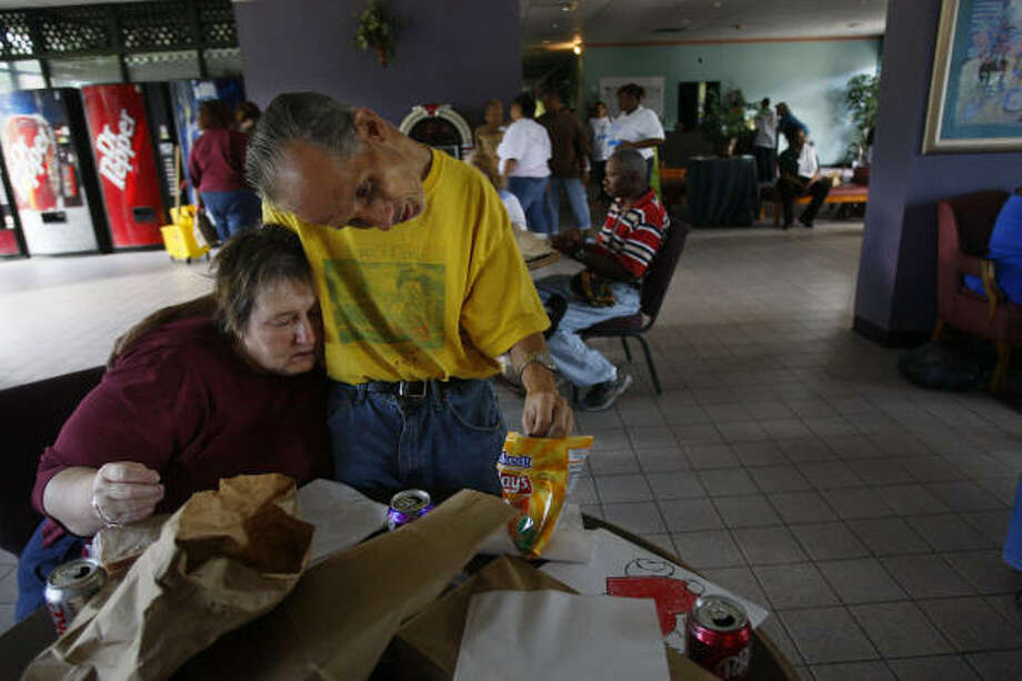 Pauline Barnes embraces James Roscoe as they eat their sacked lunch at The Center Serving People with Mental Retardation. Ninety residents were still without power Tuesday. Photo: Mayra Beltran, Chronicle