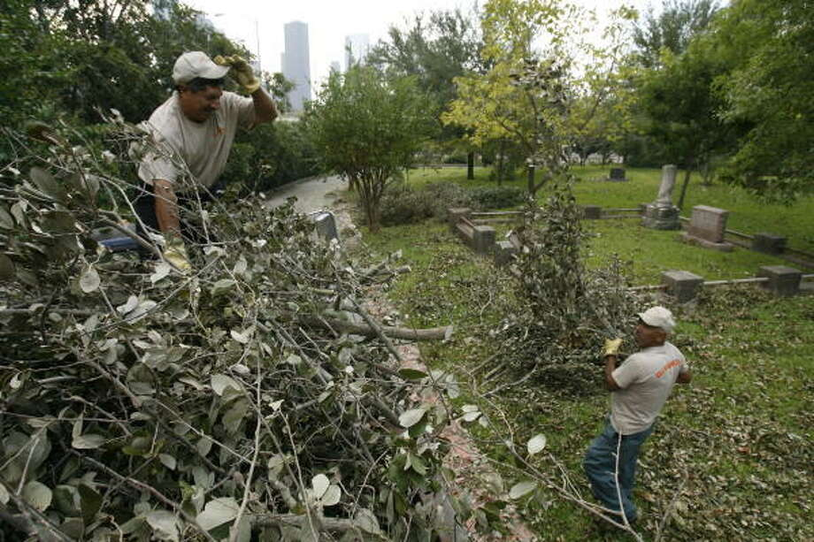Fidel Espinoza hands branches up to Natividad Ruiz on the top of a truck bed as the two work to clean up downed trees at Glenwood Cemetery on Washington Ave. Sept. 18, 2008. The cemetery lost about 100 trees and a number of statues in Hurricane Ike. See Sept. 17 photos Photo: Nathan Lindstrom, For The Chronicle
