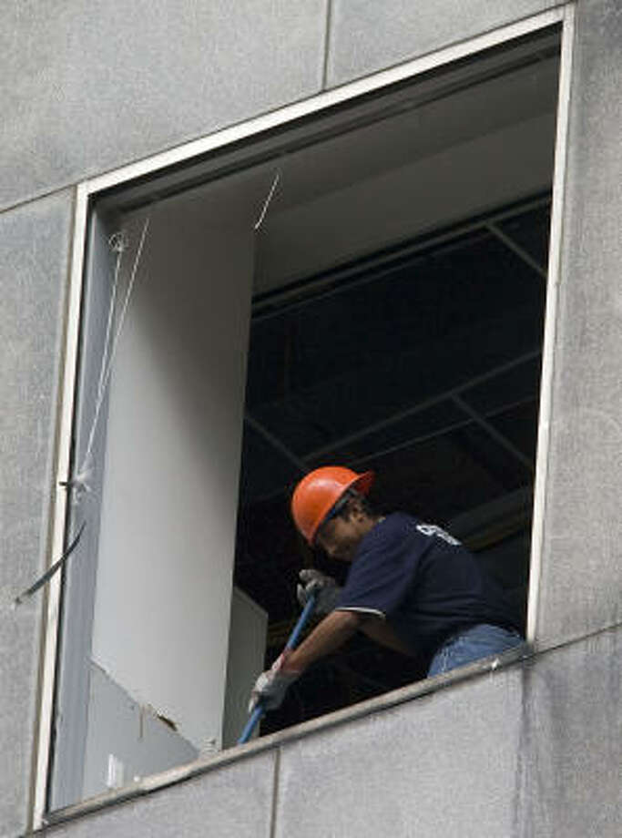 Cleanup is under way Monday at the Chase Tower in downtown Houston. Hurricane Ike blasted out many windows in the city's tallest building. Photo: James Nielsen, Chronicle