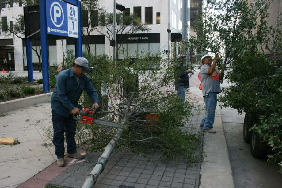 Crews were out early Monday morning clearing away tree limbs from the streets of downtown Houston. Photo: Scott Clark, Chronicle