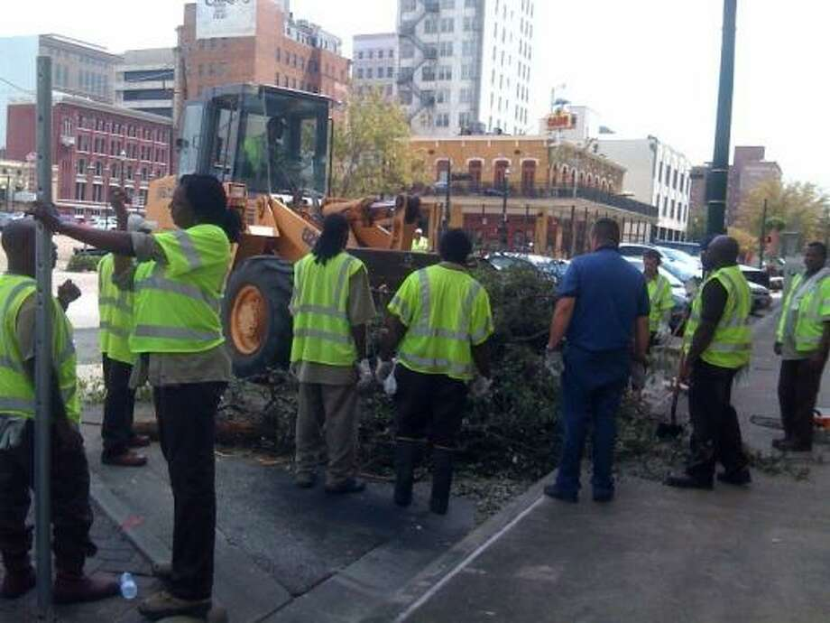 City workers clear fallen trees and branches from Prairie Street early Monday afternoon. Photo: Cory Heikkila, For The Chronicle