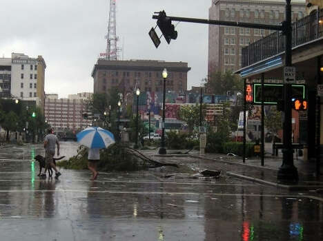 Houstonians walk their dog and survey the damage early Saturday morning in downtown Houston. Photo: Luis Perez, Chronicle