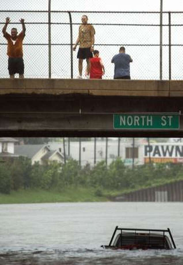 Onlookers pause on a bridge to survey floodwater covering I-45 just north of downtown Houston. Photo: Smiley N. Pool, Chronicle
