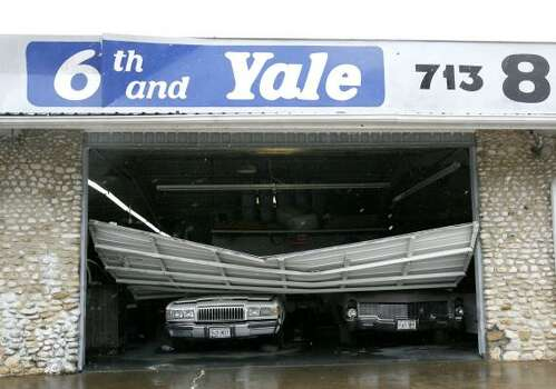 Two cars sit under a collapsed garage door at the 6th and Yale garage in the Heights. Photo: Karen Warren, Chronicle