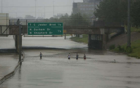 Men walk on flooded I-10 today in downtown Houston. Photo: Jay Janner, AP
