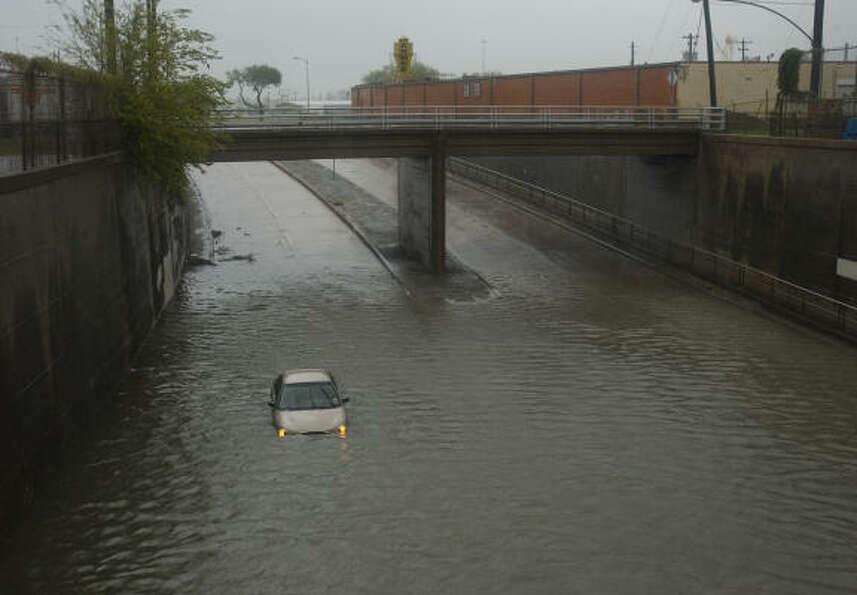 A car is stranded in high water on a street near downtown Houston.