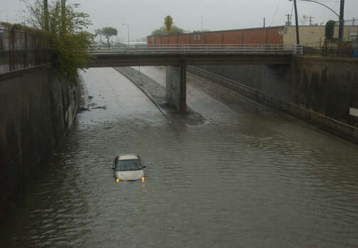 A car is stranded in high water on a street near downtown Houston. Photo: Jay Janner, AP