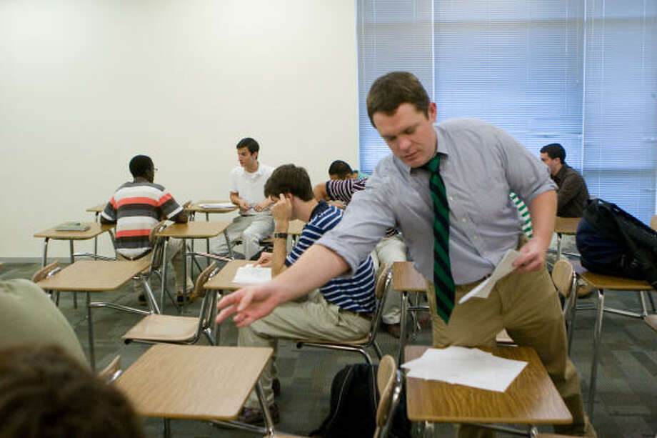 Strake Jesuit teacher  Andrew Pruett hands out a surveys to his home room. Photo: R. Clayton McKee, For The Chronicle