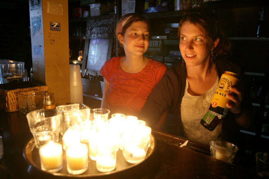 Sisters and fellow bartenders Charlotte, left, and Jesi Chaney cheerfully serve cold beers by candlelight at Little Woodrows in the Rice Village. Photo: Bill Olive, For The Chronicle