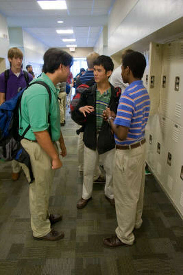 Strake Jesuit students Stephen Skerl, 16; Justin Cheung, 17; and Marcus Barnett, 16, catch up in a school hallway. Photo: R. Clayton McKee, For The Chronicle