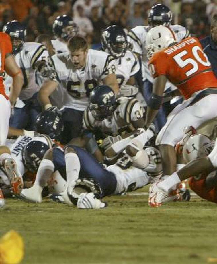 Miami and Florida International players fight during their game last October. A total of 31 players were sanctioned for the fracas, and both teams' coaches were replaced following the season. Photo: WILFREDO LEE, ASSOCIATED PRESS