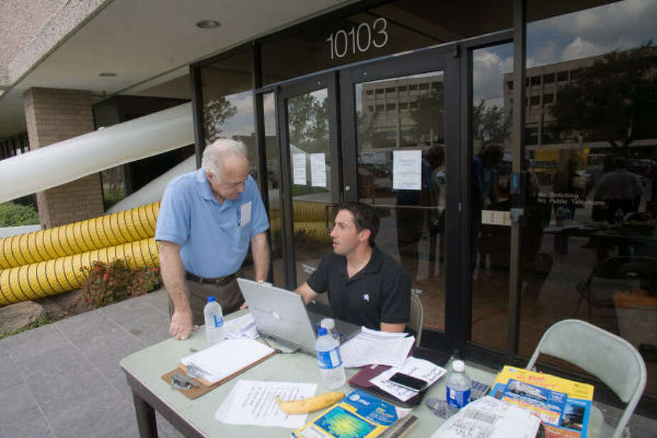 Brays Oaks Management District Community Services Director Jim Myers, right, talks to leasing director Jeremy Reeves outside Brays Oaks Towers, 10103 Fondren. The building remains without power after Hurricane Ike and has been temporarily closed while repair and restoration is completed. Photo: R. Clayton McKee, For The Chronicle
