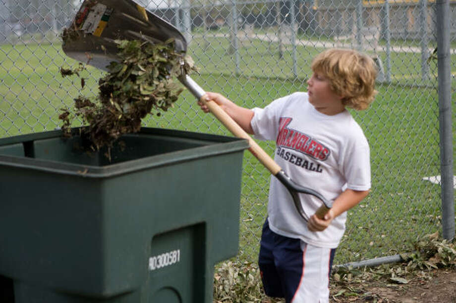 Hunter Megarity, 8, of the West U Wranglers, helps clean up the ballpark. Photo: R. Clayton McKee, For The Chronicle
