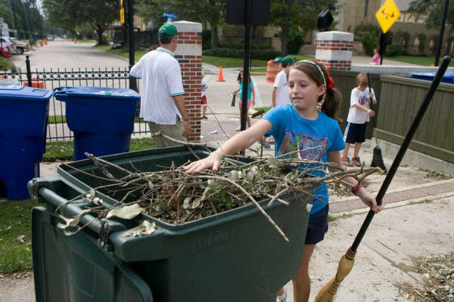 Louise McCartney, 9, a softball player, cleans up trash in the ballpark as residents of West University Place go about setting their lives and their city back in order after Hurricane Ike. Photo: R. Clayton McKee, For The Chronicle