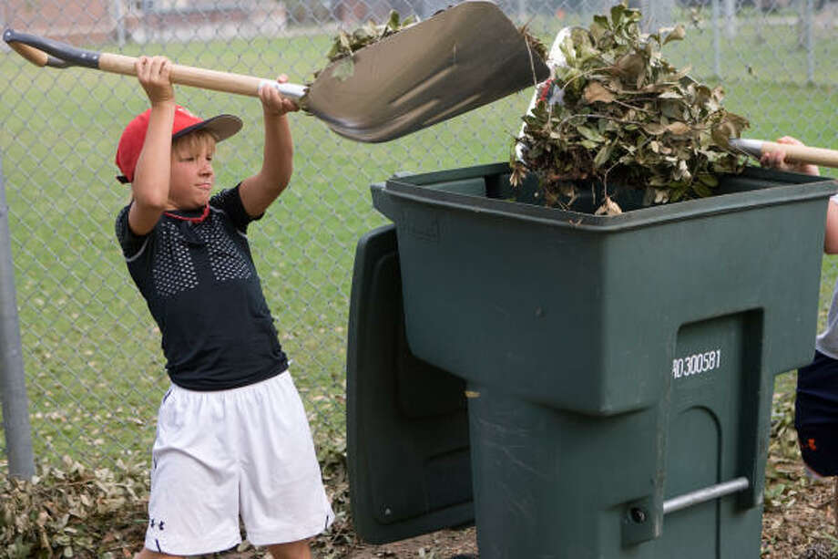 Henry Hughey, 9, of the West U Wranglers, helps clean up the ballpark. Photo: R. Clayton McKee, For The Chronicle