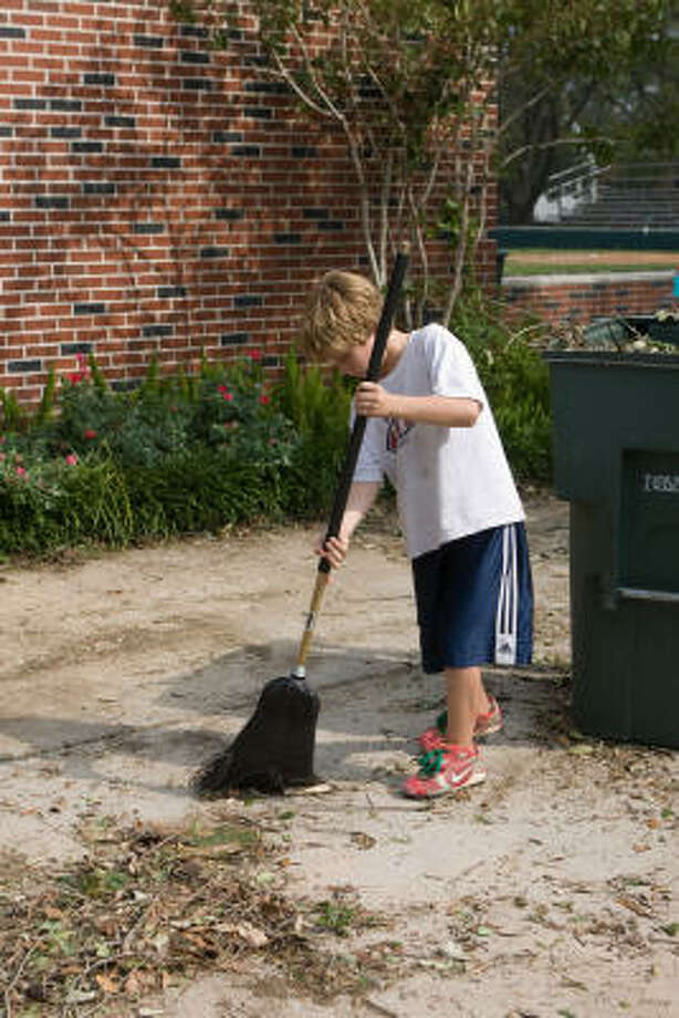 Matthew Galtney, 10, helps clean up the West University Little League ballpark. Photo: R. Clayton McKee, For The Chronicle