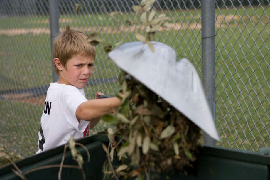 Will Mercer, 9, of the West U Wranglers, helps clean up the ballpark. Photo: R. Clayton McKee, For The Chronicle