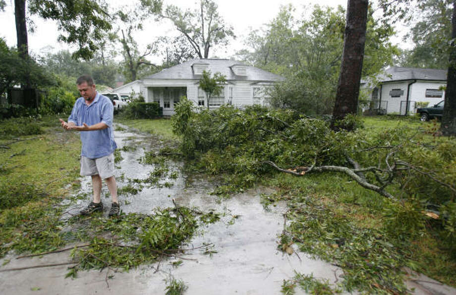 Paul Kopecky wipes his hands off after tries to clear the tree limbs from his girlfriend's Garden Oaks. Photo: Karen Warren, Chronicle