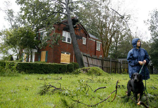 Thelma Elizalde and her dog Cole survey the damage done to her Garden Oaks home after a tree fell on it. Photo: Karen Warren, Chronicle