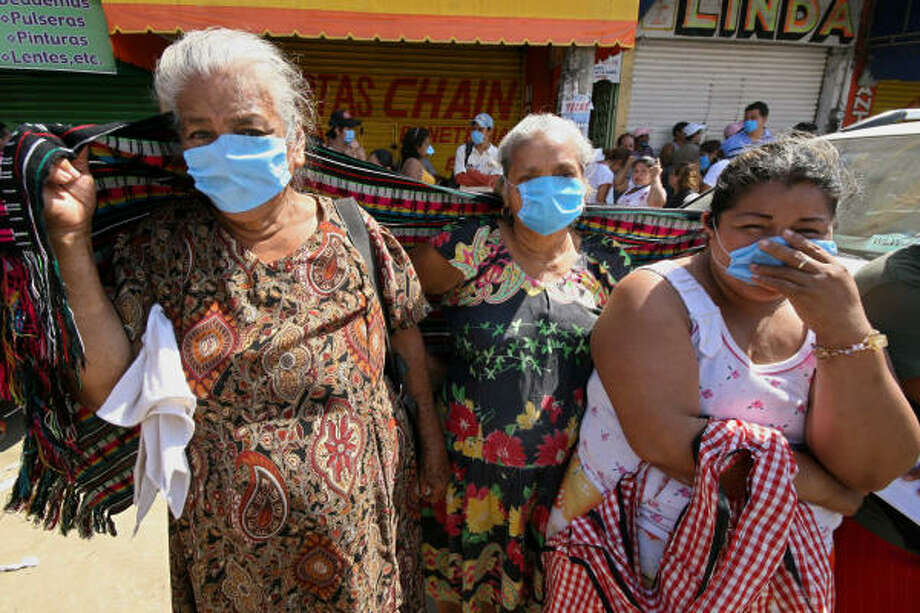 Residents use surgical masks Nov. 12 due the odor in the streets of Villahermosa, the capital of Tabasco state, after heavy floods. Photo: GILBERTO VILLASANA, AFP/Getty Images