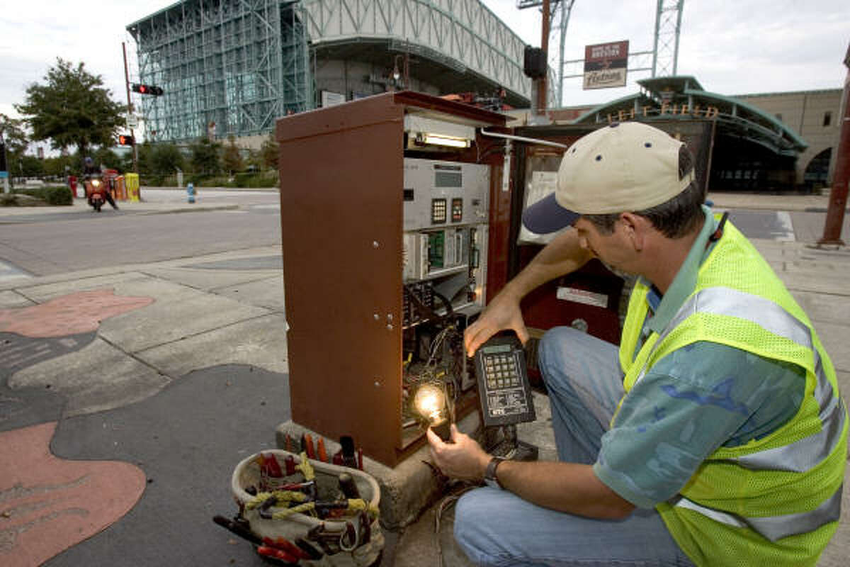 Timothy Bales, lead traffic signal technician for the City of Houston, uses a Real Time Clock to synchronize the traffic lights in the Crawford area corridor at Crawford and Prairie on Nov. 20, 2007.