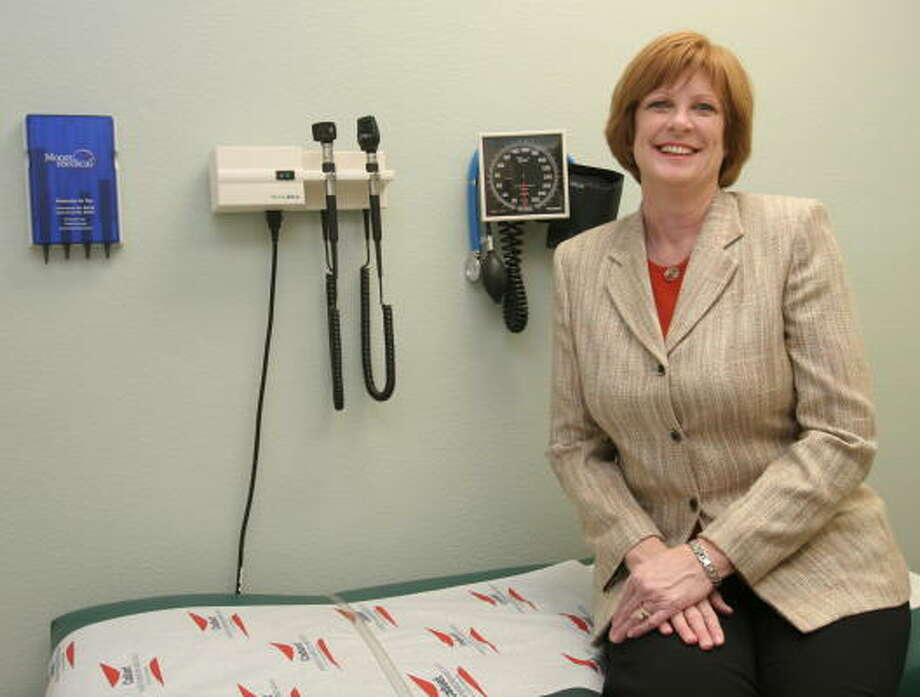 Christ Clinic, 5504 First St. in Katy, held its ribbon cutting Feb. 27.  Maribeth Walsh, executive director, sits on an examining table in a patient room at the clinic. Photo: Suzanne Rehak, For The Chronicle