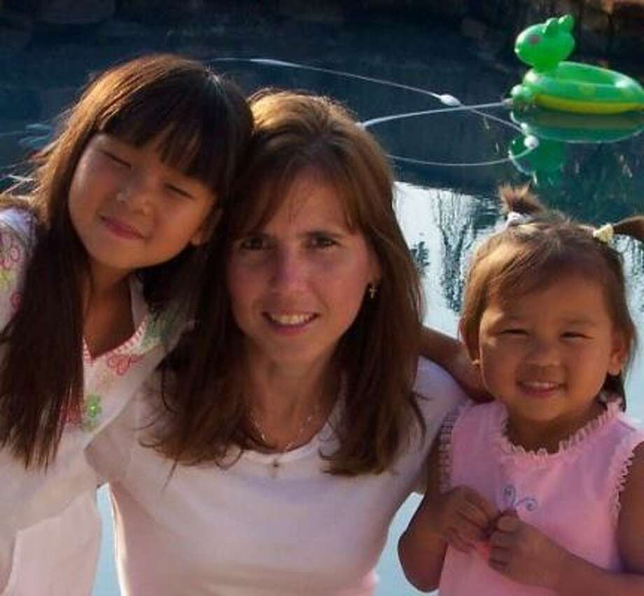 Katha Greer Rennison, who adopted her daughters, Hannah, left, and Zoe, both from China, suffered from cystic fibrosis. Photo: FAMILY PHOTO