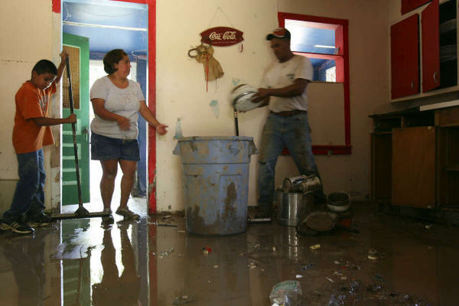 Members of the Mares family Juan, 9, his mother Georgia and his father Robert, from left, clean up the remains of their kitchen after Saturday's flood in D'Hanis. Photo: Edward A. Ornelas, AP