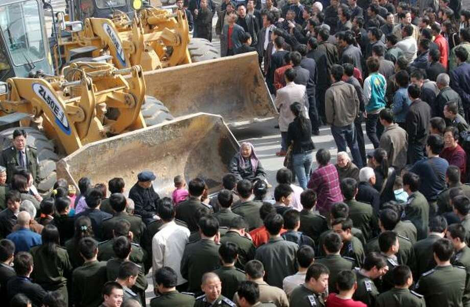 Villagers block bulldozers during a property dispute in China's central Henan province in April. The Asian Development Bank reports that the growing gap between rich and poor in Asia may be fueling unrest. Photo: Anonymous, ASSOCIATED PRESS FILE