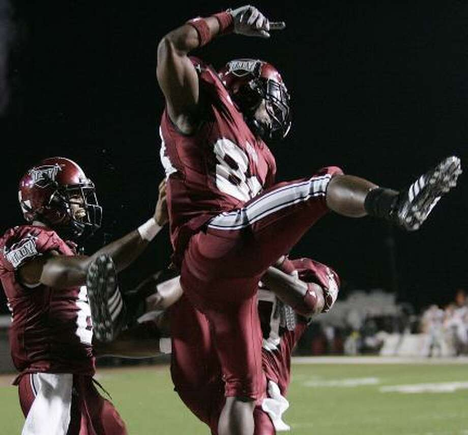 Troy receiver Kennard Burton celebrates a touchdown with teammates Gary Banks, left, and Gerald Tate. Photo: DAVE MARTIN, ASSOCIATED PRESS