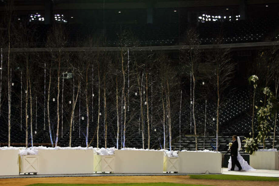 A couple enters the field at Minute Maid Park to get married Sunday. Photo: Eric Kayne, Chronicle