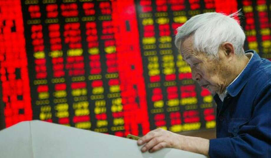 Monitors show stock prices in Shanghai, China. Shares tumbled nearly 5 percent Wednesday in China's biggest one-day loss in eight months. Photo: ASSOCIATED PRESS FILE