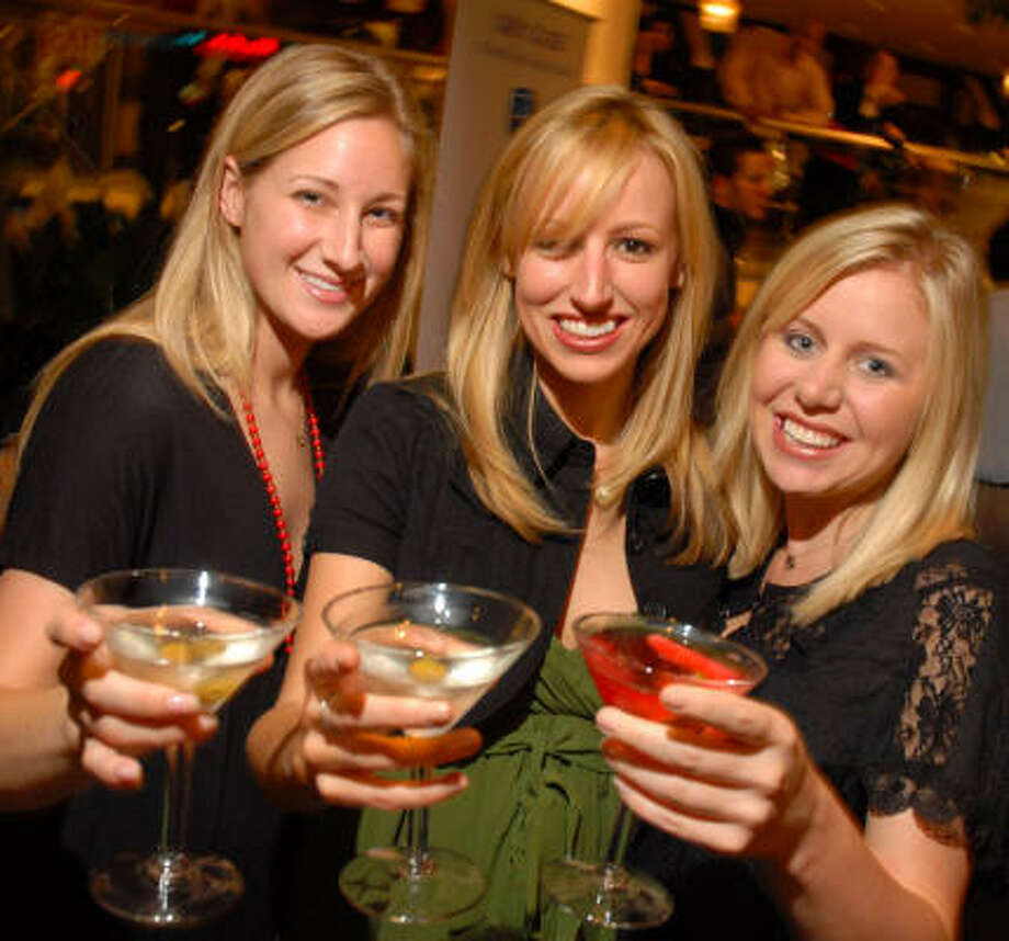 Sondra Throckmorton, from left, Sarah Barry and Kari Musslewhite raise their glasses in a salute to the season's fashion and fun. Photo: Dave Rossman, For The Chronicle